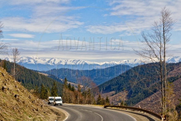 Two white vans on a winding mountain road