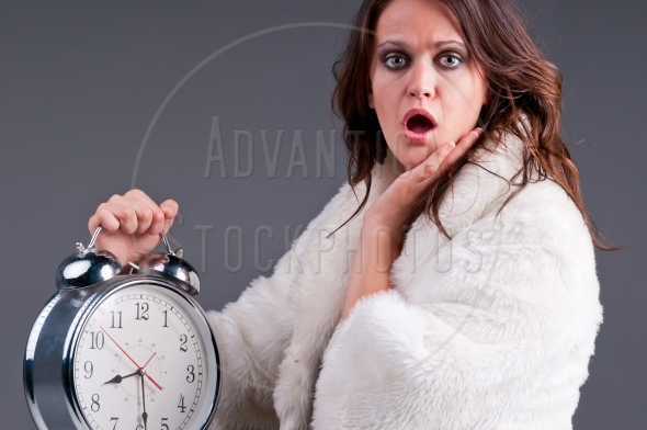 Startled woman with a large alarm clock