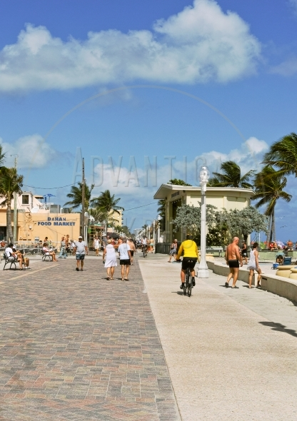 Tourists stroll on Hollywood beach boardwalk