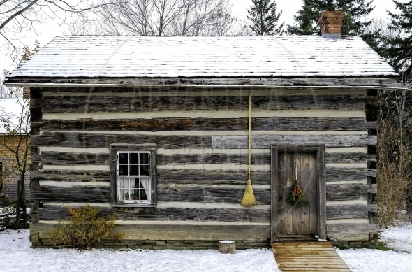 Old log home with a broom on the wall