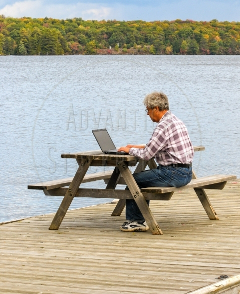 Man working on a laptop at a picnic table