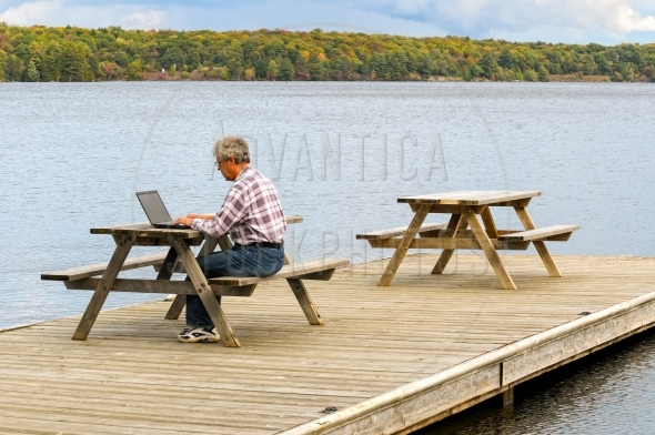 Man working on a laptop computer at a lake