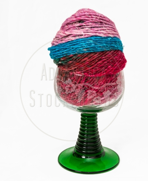 Colorful knitting yarn in a wine glass