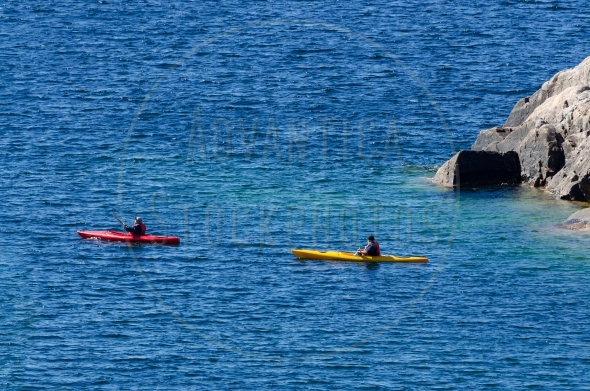 Two kayaks paddling beside a cliff